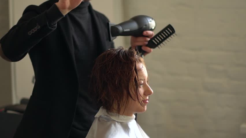 Hairdresser dries the hair of a young girl in a beauty salon. Face in profile, backlit. | Shutterstock HD Video #1020228295