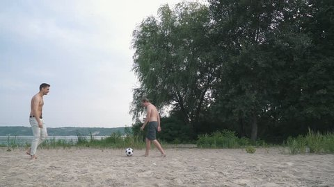 Two friends playing football on the sand near the river Competition between people Friends have a fun together Spending time outdoors Active lifestyle