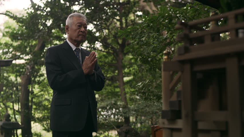 Japanese senior citizen in suit clapping and bowing in front of a shrine in a beautiful green garden with soft natural lighting. Medium shot on 4k RED camera.
