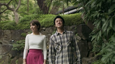 Happy Japanese couple walking together down stone steps through a beautiful garden with soft natural lighting. Wide to Medium shot on 4k RED camera.