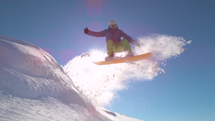 SLOW MOTIONWARP, LENS FLARE, CLOSE UP: Pro snowboarder jumping in fresh snow, spraying snowflakes over sun. Male freerider takes off in the air on his snowboard on sunny day on the mountain slopes.