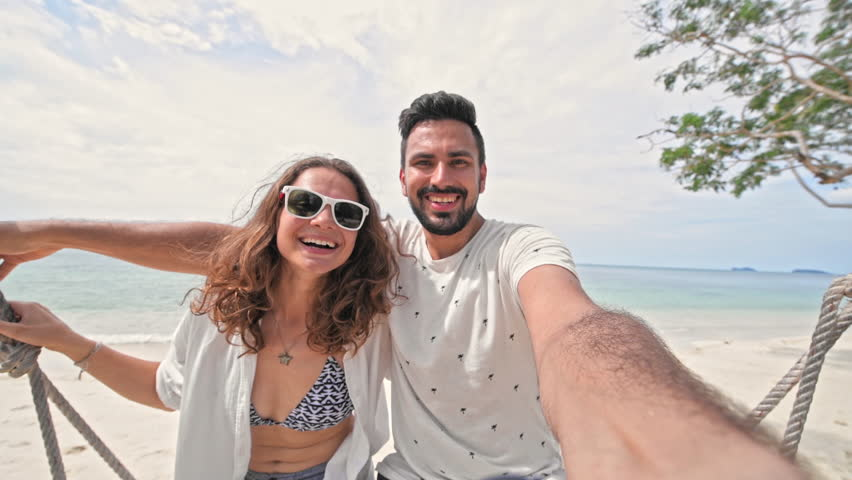 A young couple swinging on a swing and shoot themselves on camera in a tropical beach. Couple in love on a beach swing by the sea in southeast Asia. Selfie | Shutterstock HD Video #1020272035