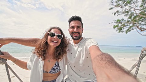 A young couple swinging on a swing and shoot themselves on camera in a tropical beach. Couple in love on a beach swing by the sea in southeast Asia. Selfie