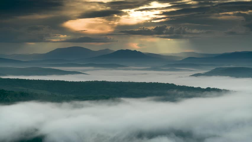 Mountain silhouettes between moving clouds in the sky and down in the valley #1020314845