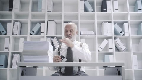 Office worker doing a boring repetitive job: he is stamping a pile of paperwork, video montage