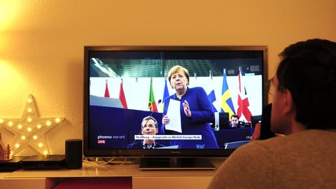STRASBOURG, FRANCE - NOV 13, 2018: Man watching Phoenix German TV broadcasting live German Chancellor Angela Merkel explaining her vision about future of Europe with members of European Parliament