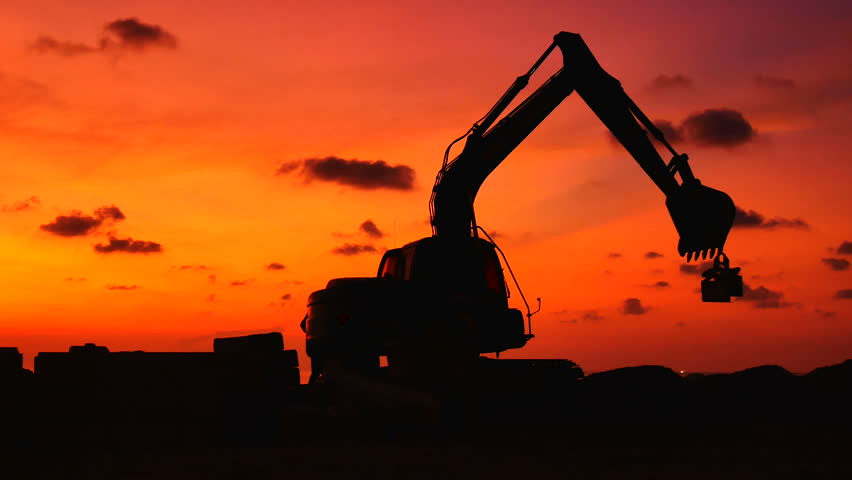 Construction Video At construction site The silhouette excavator is digging ground and lifting a large mortar with engineering and construction workers to help with colorful sunset