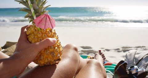 POV of woman holding pineapple cocktail girl with sexy legs on beach self shot