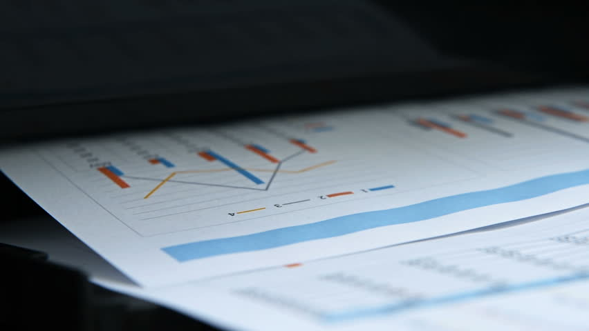 Business Report And Investment Charts Printed On Black Printer.
