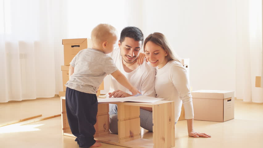 Family with little boy reading instruction and assemble furniture together at living room of new apartment pile of moving boxes on background | Shutterstock HD Video #1020426865