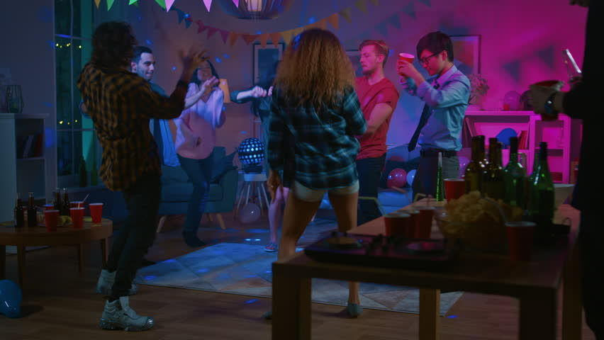 At the College House Party: Diverse Group of Friends Have Fun, Dancing and Socializing. Boys and Girls Dancing in the Circle. Disco Neon Strobe Lights Illuminating Room. | Shutterstock HD Video #1020453445