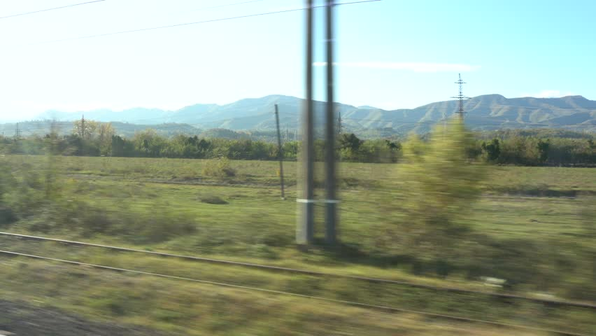 View from the high speed train at beautiful Georgian landscapes with hills and forest. Window view from car, bus, train. Traveling from train on a sunny day. Train from Tbilisi to Batumi, Georgia