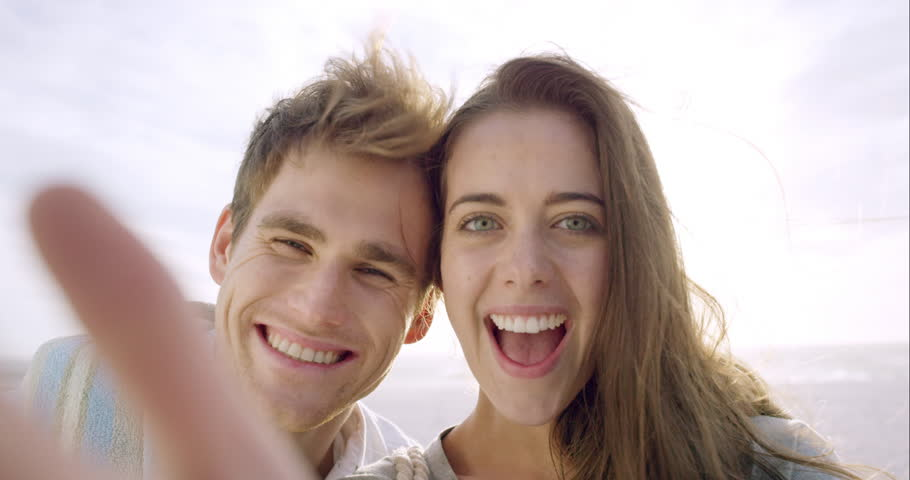 Happy couple taking selfie on beach at sunset using phone smiling and spinning enjoying nature and lifestyle on vacation | Shutterstock HD Video #10205045