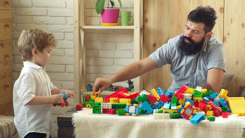 Father and son with happy faces create colorful constructions with toy bricks. The boy and his father play with the designer lego. Family and childhood concept