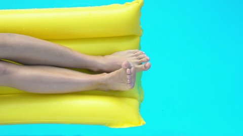 Close up of legs on inflatable mattress playing with water in pool, vacation