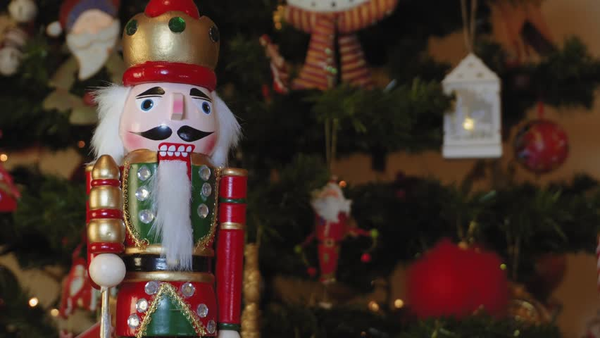 Large tin nutcracker soldier on a Christmas tree with blurred background. Seasonal toy figure before an illuminated artificial Christmas tree with lights ...