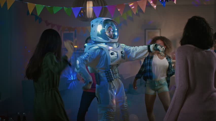 At the College House Costume Party: Fun Guy Wearing Space Suit Dances Off, Doing Robot Dance Modern Moves. With Him Beautiful Girls and Boys Dancing in Neon Lights. | Shutterstock HD Video #1020543025