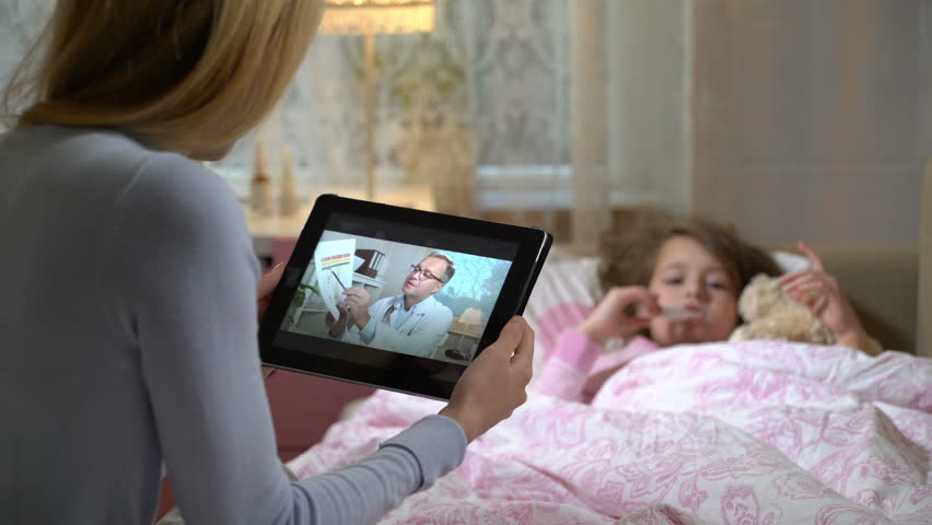 Medicine online. Mom with a little sick daughter gets a doctor's advice using video chat at home. The doctor showing her the results of medical tests | Shutterstock HD Video #1020553675