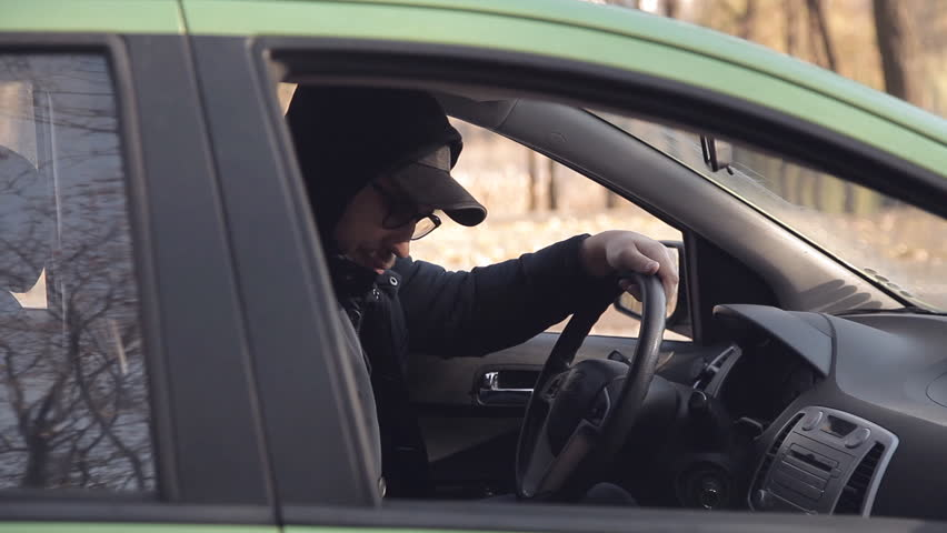 A private detective or a spy conducts surveillance of the object of surveillance. A man secretly taking pictures from the car window | Shutterstock HD Video #1020566695