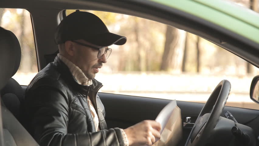 A private detective or a spy conducts surveillance of the object of surveillance. A man secretly taking pictures from the car window | Shutterstock HD Video #1020566725