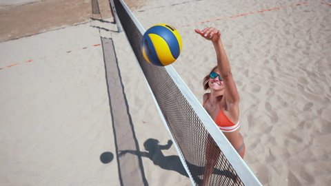 SLOW MOTION, CLOSE UP: Cheerful Caucasian girl in bikini smashes the ball over the volleyball net while playing beach volley during her fun summer holiday. Smiling young female beach volleyball player