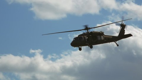 Military helicopter on battlefield flies overhead passing in slow-motion. Blackhawk chopper. Blue skies and clouds.
