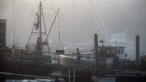 ROCKPORT, MAINE circa July 2017 - Lobster fishing boat unloading its daily catch in early morning light at sunrise in a foggy and quaint New England harbor.