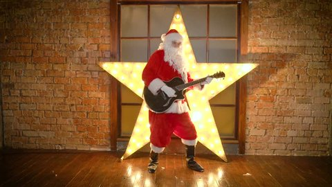 Santa Claus rock star, plays christmas songs by guitar, have fun, celebrate holidays