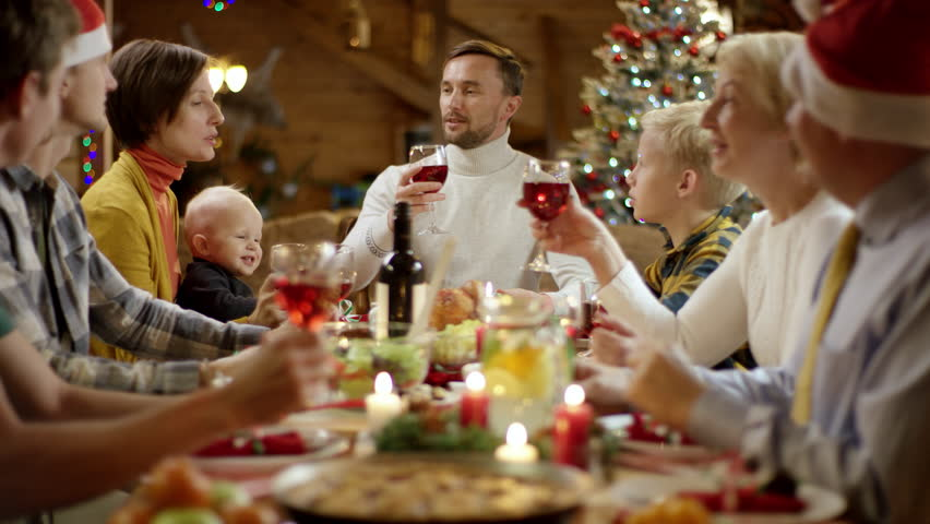 Head of the family speaks a toast by Christmas table and everyone is clinking | Shutterstock HD Video #1020655915