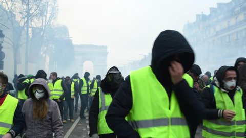 Paris, France - December 8 2018: Protesters protect and run away for cover from tear gas launched by riot police during a Yellow Vests (Gilets jaunes) protest against living costs and rising prices