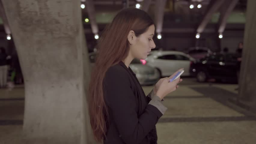 Beautiful girl chatting on smartphone while walking in night city. Dolly shot. Side view of young businesswoman texting on smartphone outdoors. Using gadget concept | Shutterstock HD Video #1020703285