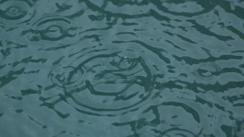 Heavy rain on water shooting. Raindrops fall into the water in slow motion.