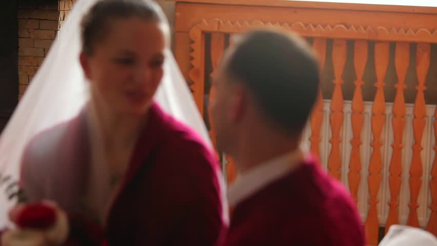 Wedding couple in love warming up in red sweaters by the fireplace. Bride and groom relax and kiss by warm fire and warming up in log wooden cottage. Winter christmas holidays and honeymoon concept. | Shutterstock HD Video #1020725605