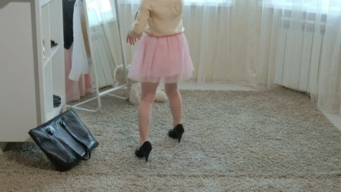 cheerful little girl with pigtails in a pink skirt tries on mother's shoes on heels and dances in front of a mirror with a bag, mother's wardrobe 4k