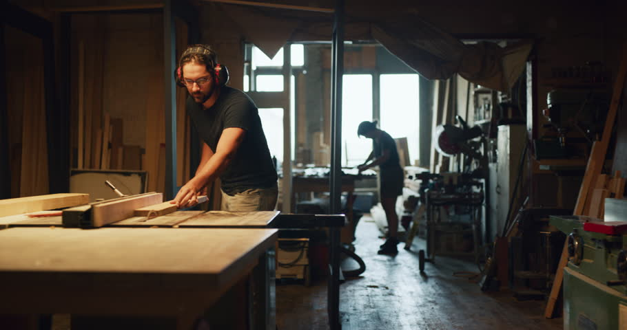 Carpenter woodworker cuts wood on saw in factory atelier during the day. Long to medium shot with warm lighting on 4K RED camera.