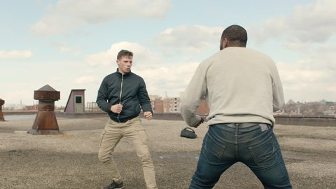 Caucasian man and African American man fight on a warehouse rooftop with hard kicks and punches in overcast sunlight. Medium shot in 4K with an Alexa Mini camera