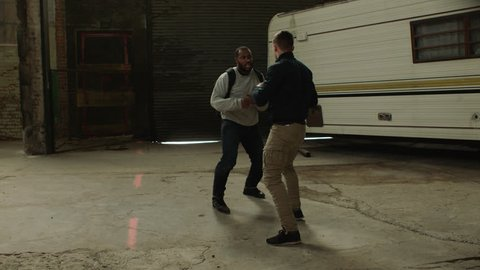 Two angry men using martial art techniques fight in front of an abandoned camper trailer in moody lighting. Medium shot in 4K with an Alexa Mini camera
