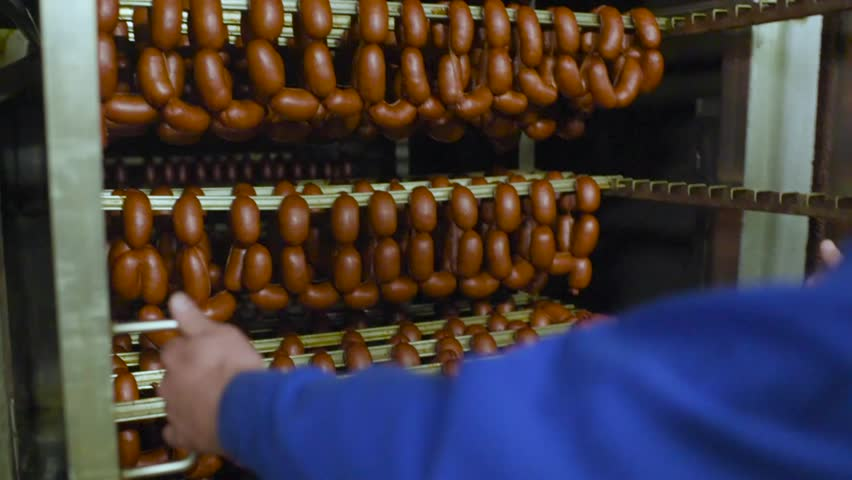 Mouthwatering smoked sausages on the background of a meat factory or butcher shop | Shutterstock HD Video #1020774265