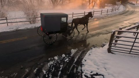 A horse-drawn Amish buggy travels through the snow-covered Pennsylvania countryside toward the Hunsecker's Mill Covered Bridge at sunset. Concept: winter, holidays, tradition, nostalgia, ?cold, snow