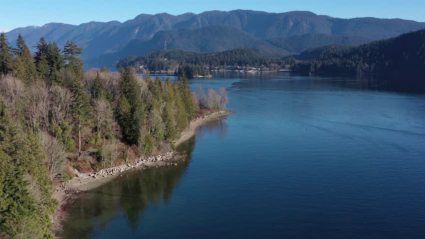 Aerial view over Burrard Inlet, ocean and island with boat and mountains in beautiful British Columbia. Canada. | Shutterstock HD Video #1020790435