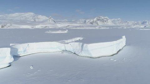 Arctic Polar Frozen Ocean Aerial View. Snow Covered Antarctica Landscape. North Nature Coastline Glacier. Cold Winter Iceberg Locked in Ice. Footage shot in 4K (UHD).