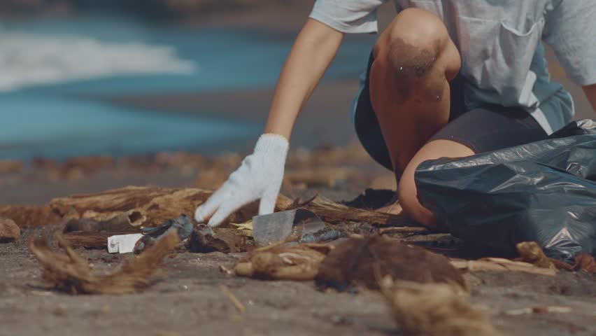 Close up of volunteers sit and picking up garbage on the beach. Cleaner collecting garbage on the black sand beach into black plastic bag. Volunteers cleaning the beach. Tidying up rubbish on beach | Shutterstock HD Video #1020794275
