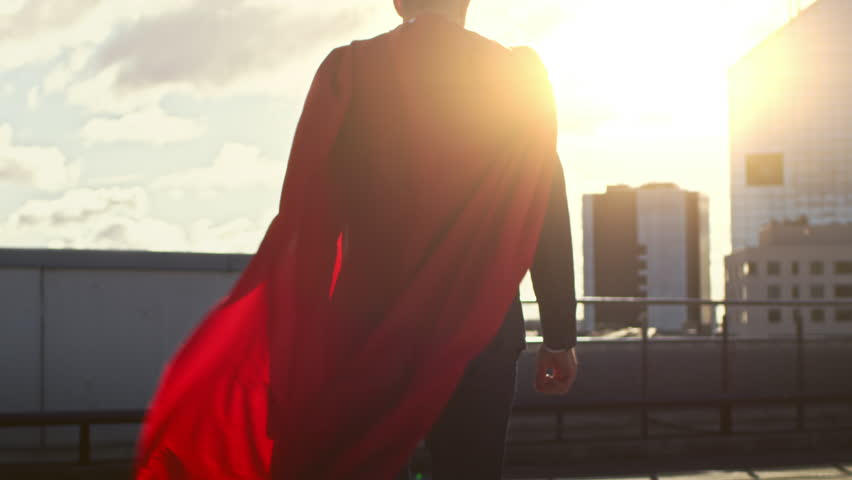 Superman WIth Red Cape Blowing in the Wind Walks on the Roof of a Skyscraper, Looking into the Sunset, Ready to Save the Day. Following Back View Slow Motion Shot.