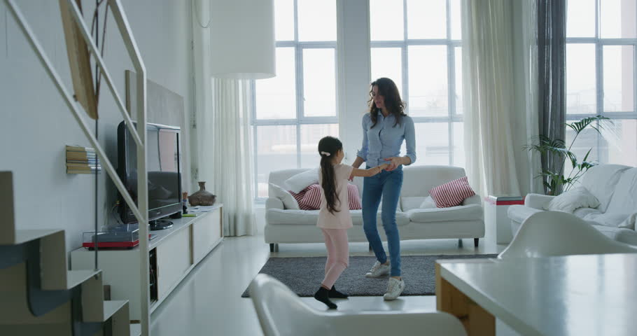 Portrait of happy mother and daughter having fun dancing together in living room in slow motion. Shot with RED camera in 8K. Concept of happy family, childhood, parenthood | Shutterstock HD Video #1020812365