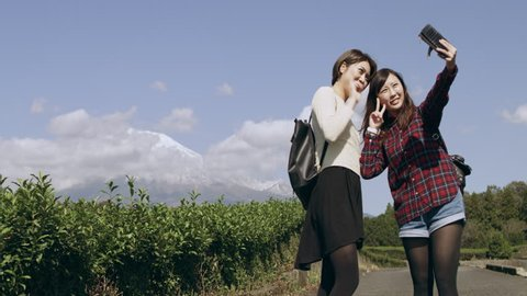 Wide shot of two happy Japanese friends taking a picture together with a mobile phone with Mount Fuji in the background in a tea plantation with soft natural lighting.