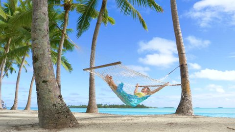 LOW ANGLE: Sleeping Caucasian woman sways in a rope hammock on the spectacular tropical white sand beach in Cook Islands. Relaxed female tourist enjoying her summer vacation by taking a nap by ocean.