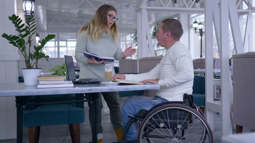 Training for invalid, happy sick student mature men in wheelchair with educator female using smart computer technology during personal lecture indoors | Shutterstock HD Video #1020863095
