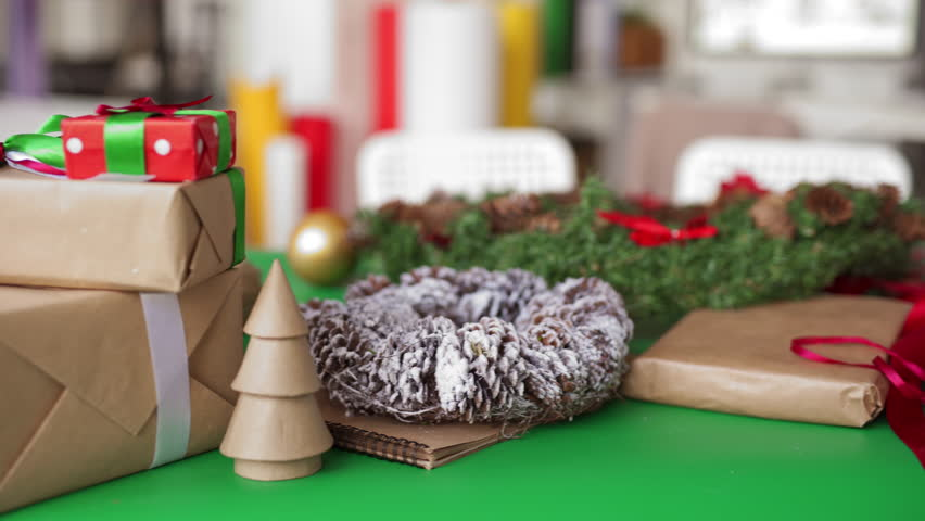 Tracking close-up shot of Christmas gift boxes, decorative wreath and craft supplies on table in art studio | Shutterstock HD Video #1020865495