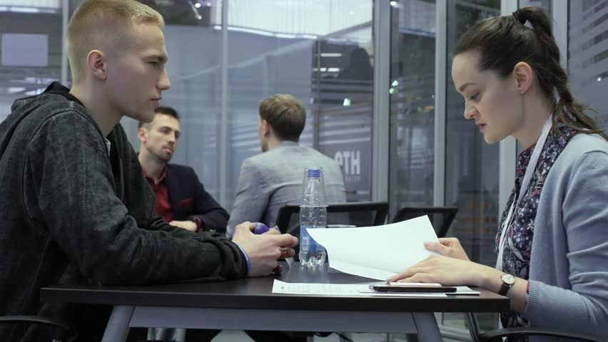 hr manager talks with a job seeker and views the resume or CV during hiring in Hi-Tech Park MINSK, BELARUS 11.24.18 #1020878125