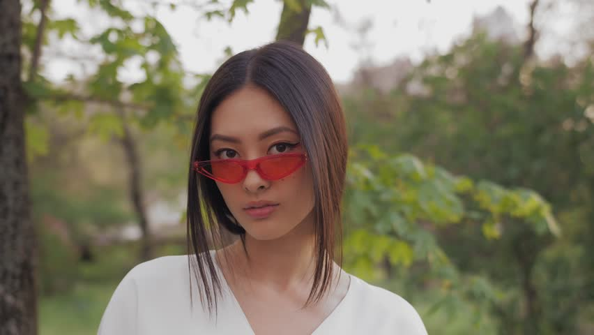 Fashion asian model portrait with creative stylish make-up wearing trendy red sunglasses white silk fashion japanese kimono standing against blurred nature backgroung. 4k slow motion footage   Shutterstock HD Video #1020885085